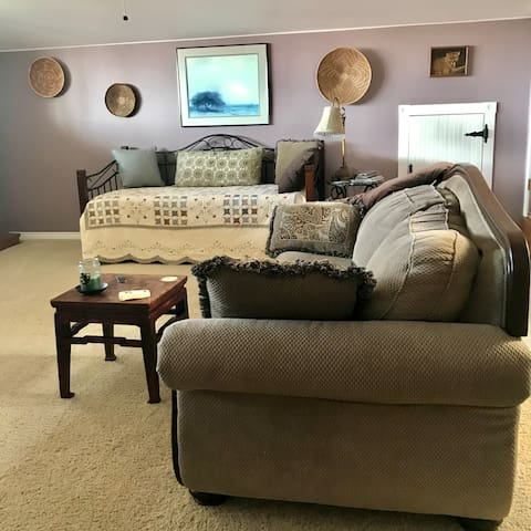Living room, with day bed, couch and loveseat. There are two decks which are accessed from this room