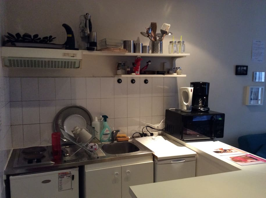 My kitchen - which is actually attached to the living room. In here you will find a fridge, a washing machine, a coffee maker, a kettle, a blender and a microwave that turns into an actually oven if needed.