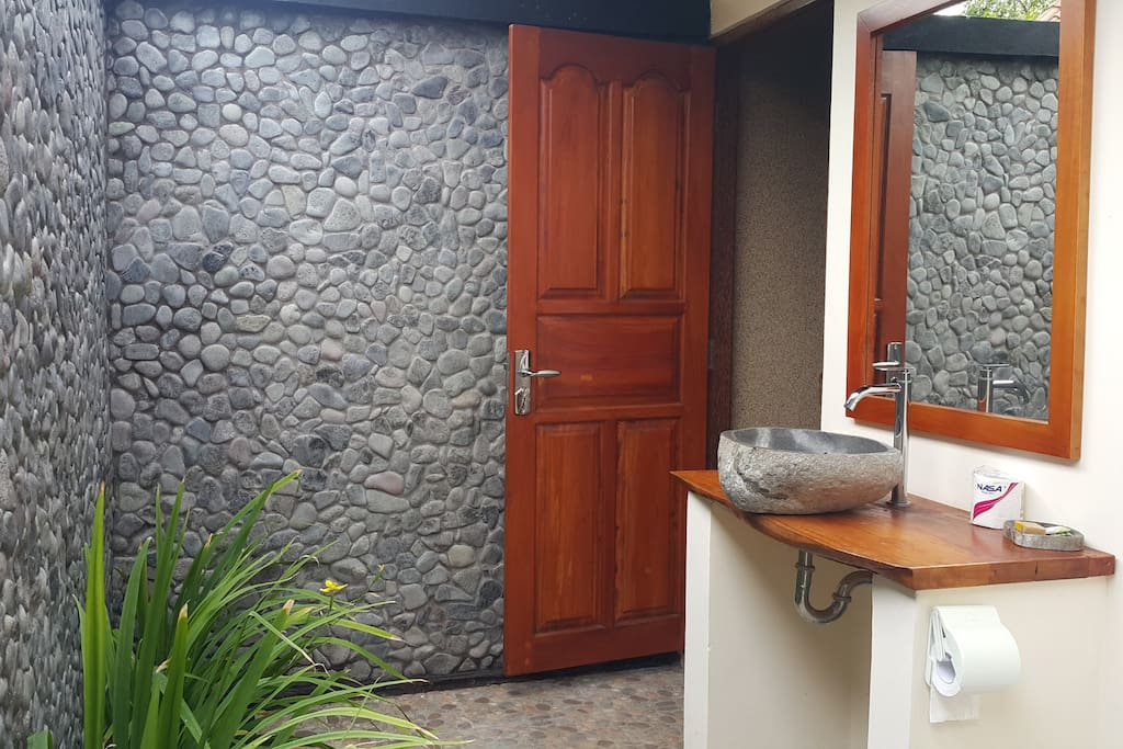 Open air bathroom with stone sink, wood from our land, and stone walls