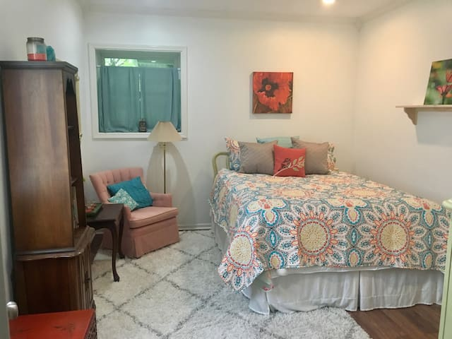 The bedroom boasts an ultra comfortable queen bed, new flat-screen TV and sitting area, adorned with stylish decor and a serene color palette.