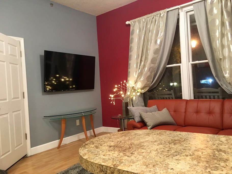 """Italian leather sectional couch to accomadate one additional adult or two children. 60"""" mounted HDTV with cable and upgraded channel listings."""