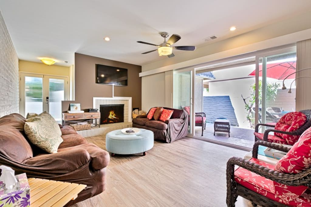 Living room with private patio access, fireplace and flat screen television.