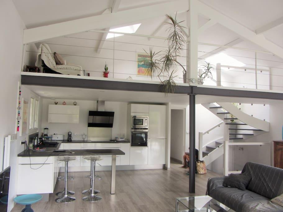 Belle pièce à vivre avec cuisine ouverte entièrement équipée avec mezzanine donnant sur salon avec Tv et box internet .