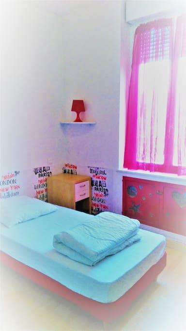 La chambre rouge : le lit et la table de nuit.