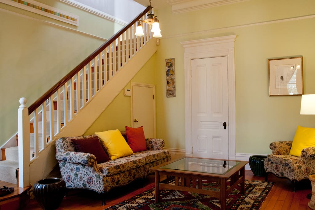 Parlor room w/ stairs leading to upstairs bedrooms and bath.