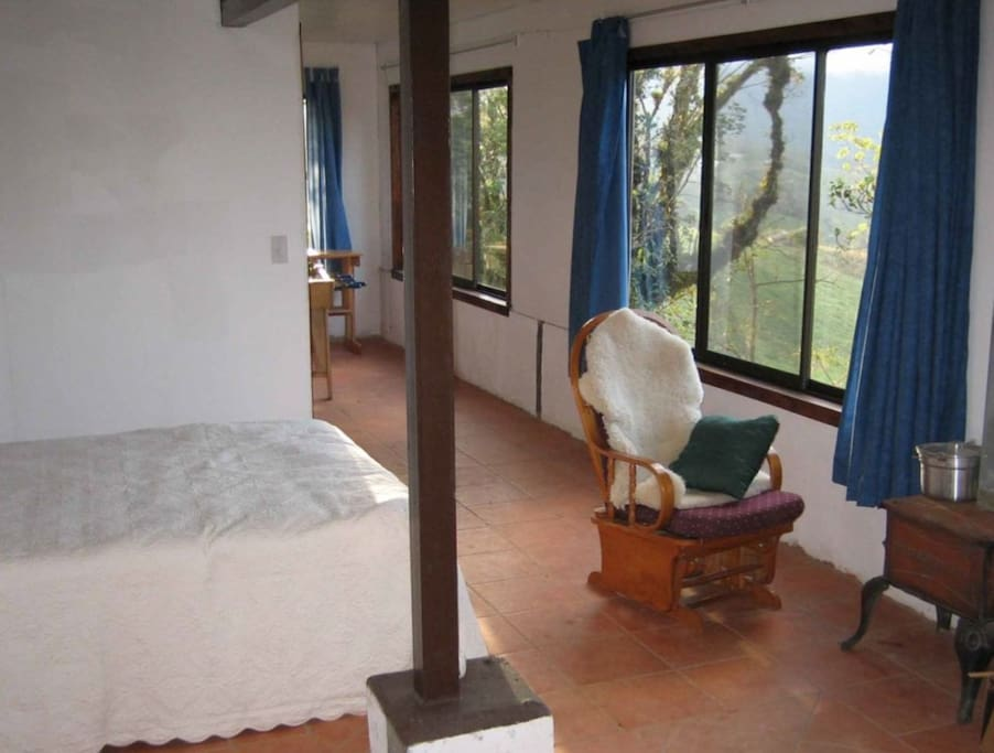 Large bedroom with multiple beds overlooking garden and jungle with views of Volcano