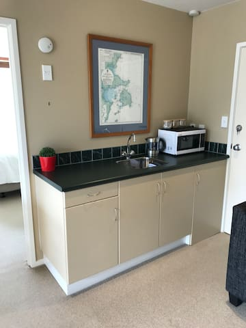 Kitchenette- containing Fridge, Microwave, Kettle (complimentary tea/coffee/sugar), cutlery, plates, cups, utensils etc.