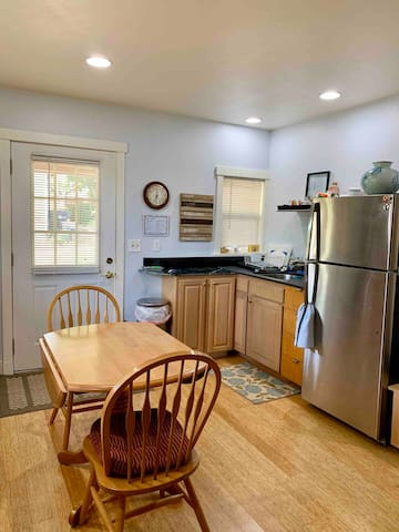 Kitchen sink with supplies stored below and cabinets equipped with kitchen ware and utensils. Mid-size fridge.