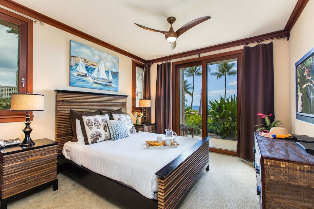 The master bedroom with king bed features flat screen wall-mounted TV, BluRay DVD player, ceiling fan and lanai access (Updated photos featuring new king bed coming soon)