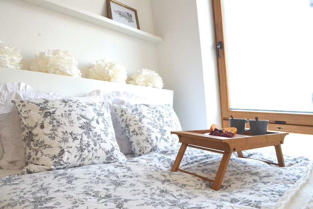 Queen size bed with a view of Vilnius skyline and a breakfast bed tray