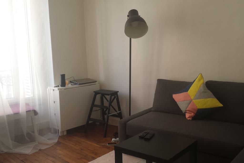 """Salon lumineux avec canapé d'angle convertible et une TV 50"""""""
