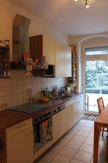 Die gegenüberliegende Kochzeile beinhaltet einen Herd, einen Ofen und einen Geschirrspüler. Von der Küche kann man direkt auf den Balkon gehen.