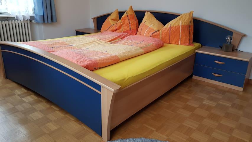 1.80m x 2.00m Bett im Schlafzimmer mit Zugang zu einem kleinen Balkon mit Sicht auf die Liechtensteiner Berge
