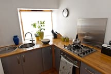 Well equipped kitchen including gas hob, electric oven, microwave, and washing machine.