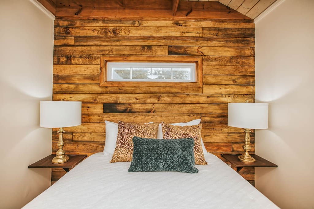 Comfortable Queen Bed with shiplap wood accent wall.
