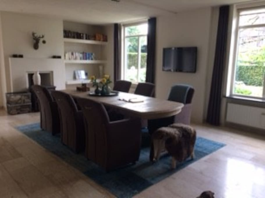 Eetkamer direct grenzend aan open keuken. TV en haard. Dining room and table directly next to open kitchen. Tv and Fire place.