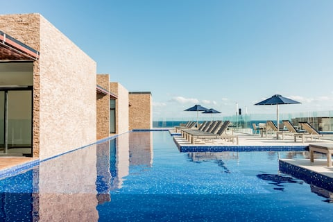 Galleggia sulla piscina panoramica con vista sull'oceano di questo elegante condominio