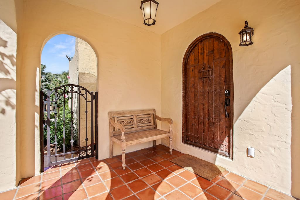 Entry porch with antique wood door and vintage iron gate