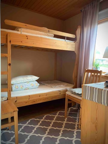 Sovrum med våningssäng på nedervåningen. I rummet finns även en byrå.