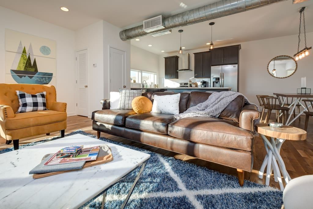 Natural light pours into the spacious living room that features 2 chic armchairs and a cozy couch.