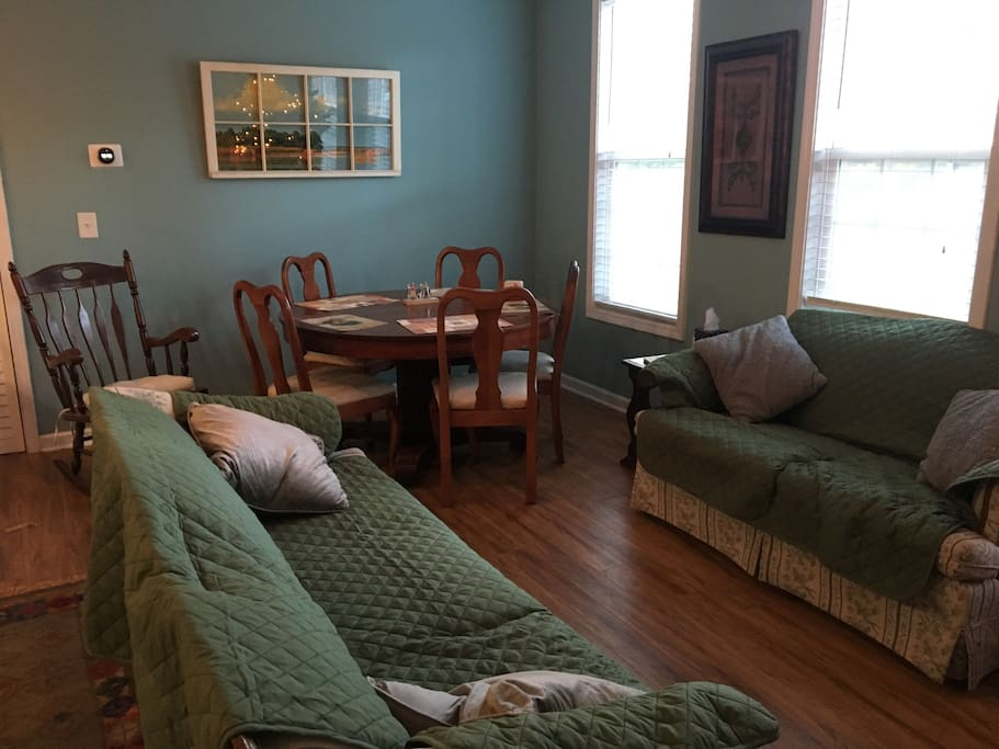 Living room and dining room, featuring pet-friendly washable couch covers and a large antique dining table. Extra inserts for the table are available to accommodate large parties.