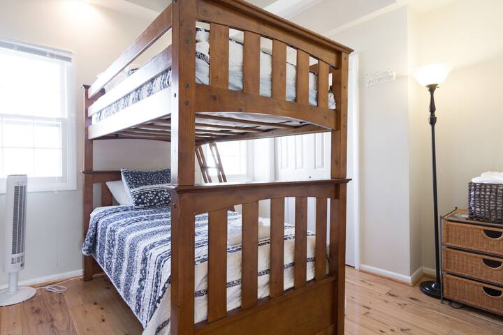 """Bunk beds, a chest of drawers, and a full closet on the lower-level of the """"Washington Suite.""""  A few toys, puzzles and children's books are in the closet."""