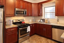 The kitchen is fully equipped with pots and pans, a coffeemaker, plates, microwave, and utensils