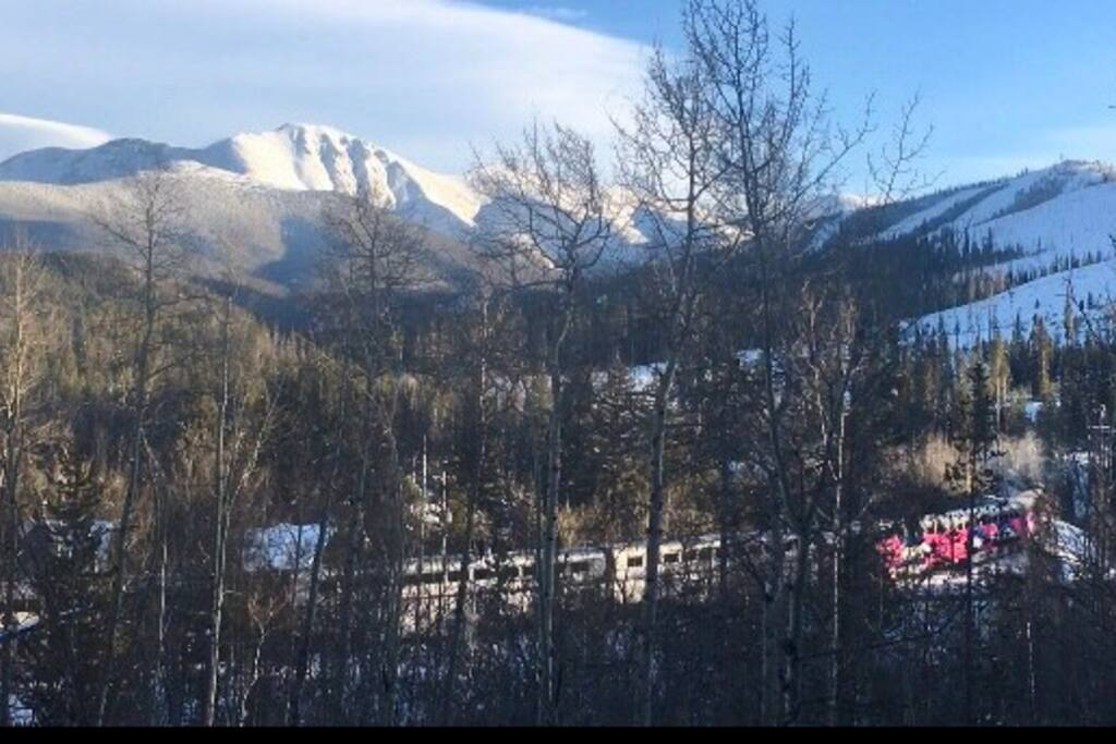 From our back deck, view of ski train, ski slopes & Continental Divide. Only a few minute drive to slopes or catch free bus shuttle steps from our door. Doesn't get any better than this!