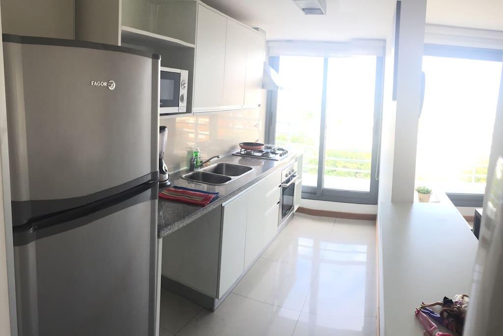 Cocina full equipada. Con heladera, microondas, cocina, licuadora, platos, utensillos, etc.