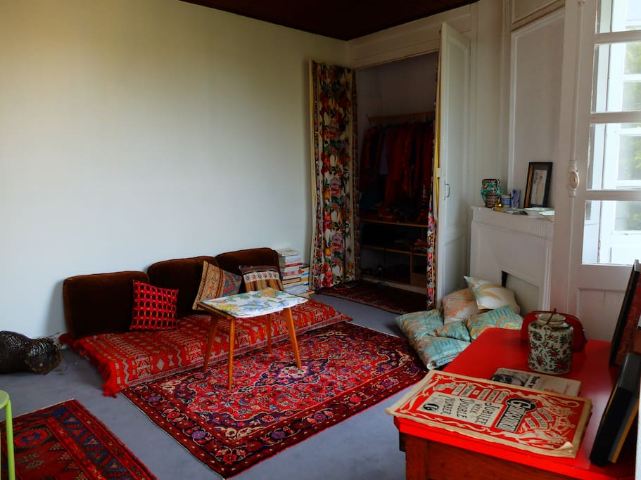 Séjour avec deux très grandes fenêtres donnant sur le cour Victor Hugo. Possibilité de faire dormir la troisième personne sur le petit lit. Le coin nuit est situé à l'arrière.