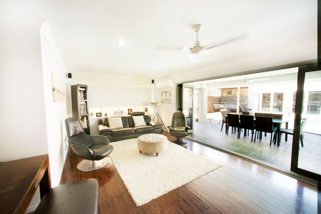 lounge room that opens up to entertaining area with pay tv and large flat screen tv