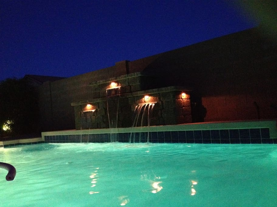 Pool at night with waterfall on.