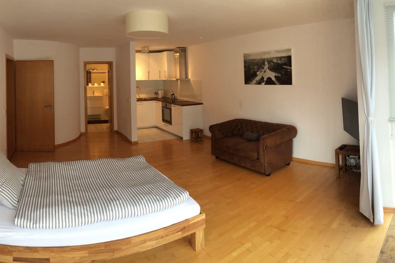 Studiowohnung mit vollausgestatteter Küche. Eingang zum Badezimmer mit Dusche/Badewann
