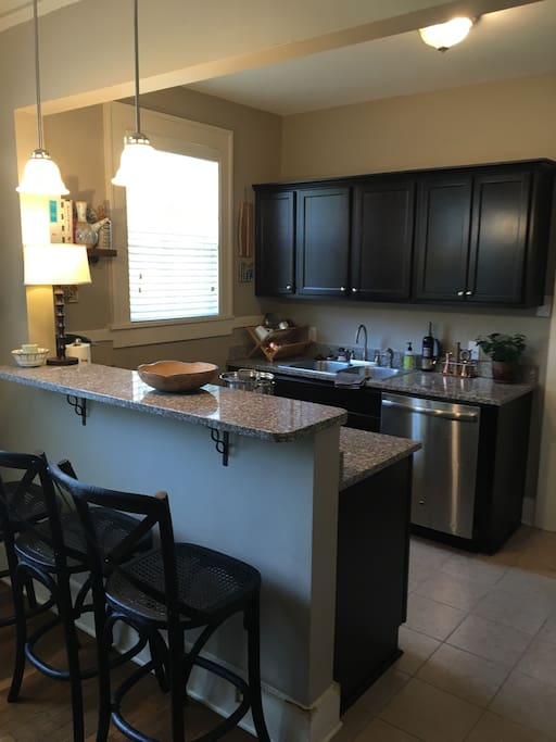 Updated kitchen with granite, stainless steel, gas cooktop and all needed utensils.  Eat in bar.