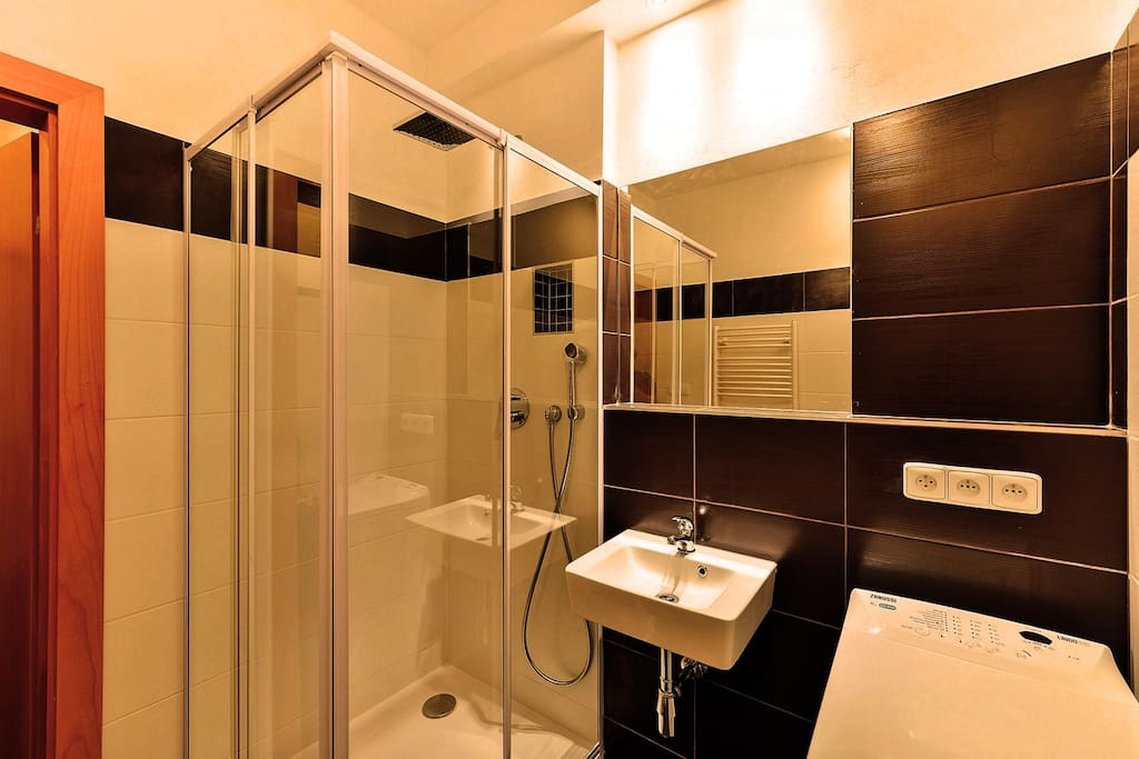 The bathroom has a shower cabinet, washing machine, wash basin, and a toilet seat.