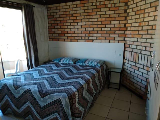 Quarto 01 - com uma cama Queen, armário, e uma pequena sacada. Cortinas com blecaute, e ar-condicionado