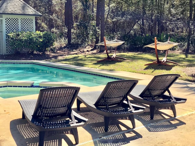 The backyard is complete with pool, hot tub, chaise lounges, hammocks, and adirondack chairs around a firepit.