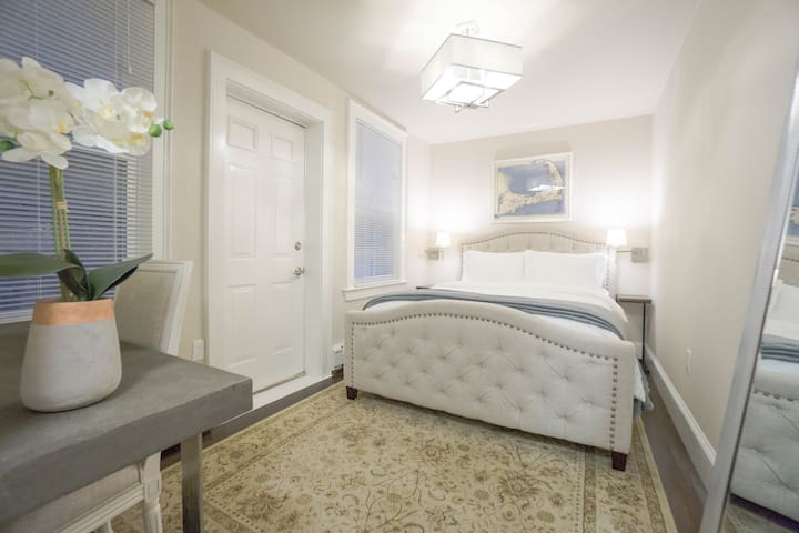 Bedroom features a queen size bed, two night stands, a small desk and chair, and a closet
