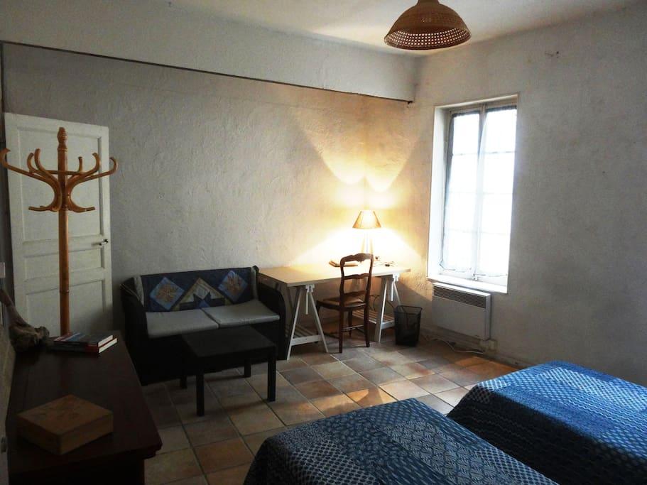 La chambre fait 20m2 et dispose d'un petit canapé et d'un bureau