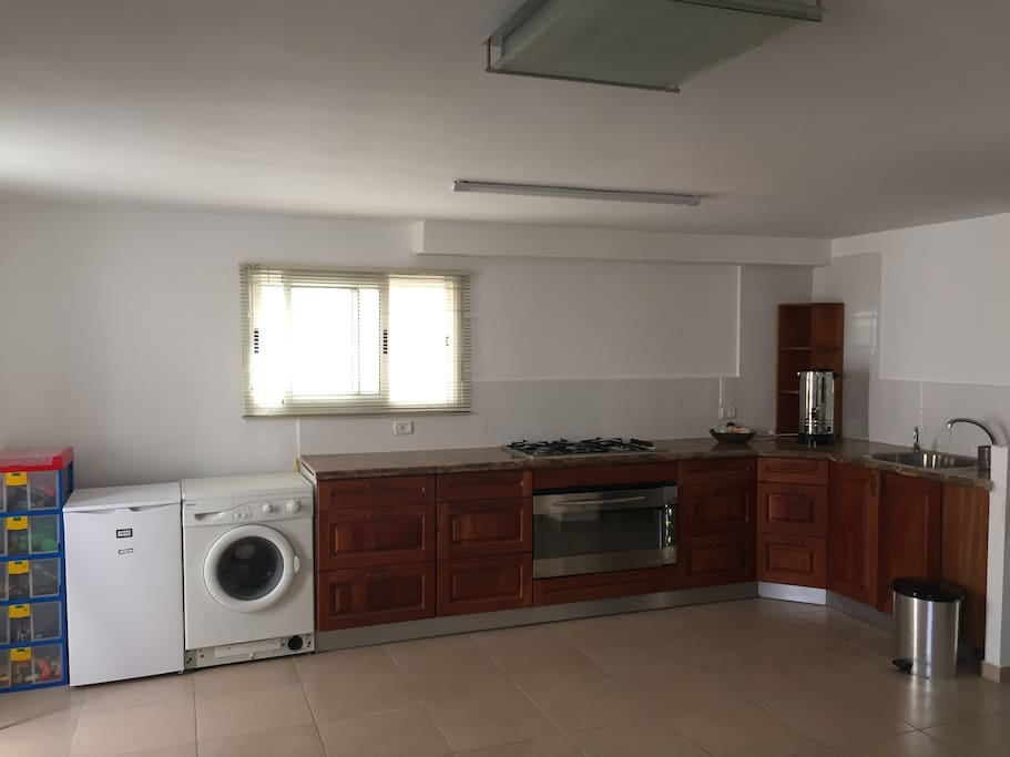 Kitchen with refrigerator, washing machine, oven, stove top