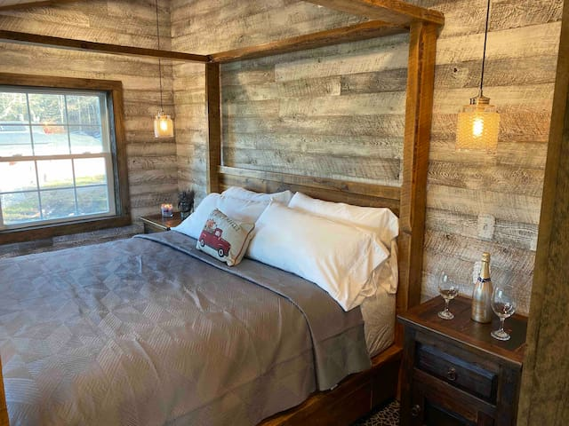 King sized four post bed made of reclaimed wood.  Night stands are also made of reclaimed wood.