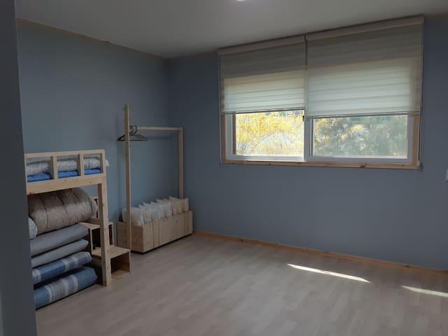 주인장 목수가 직접 제작한 이층 침대,다용도 옷걸이와 넓은 방 ,창에는 개나리와 나무가 우거져 있네요