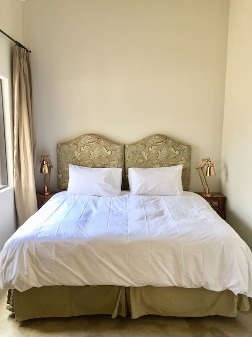 Beautifully appointed king-size bed with percale linen and design a headboard