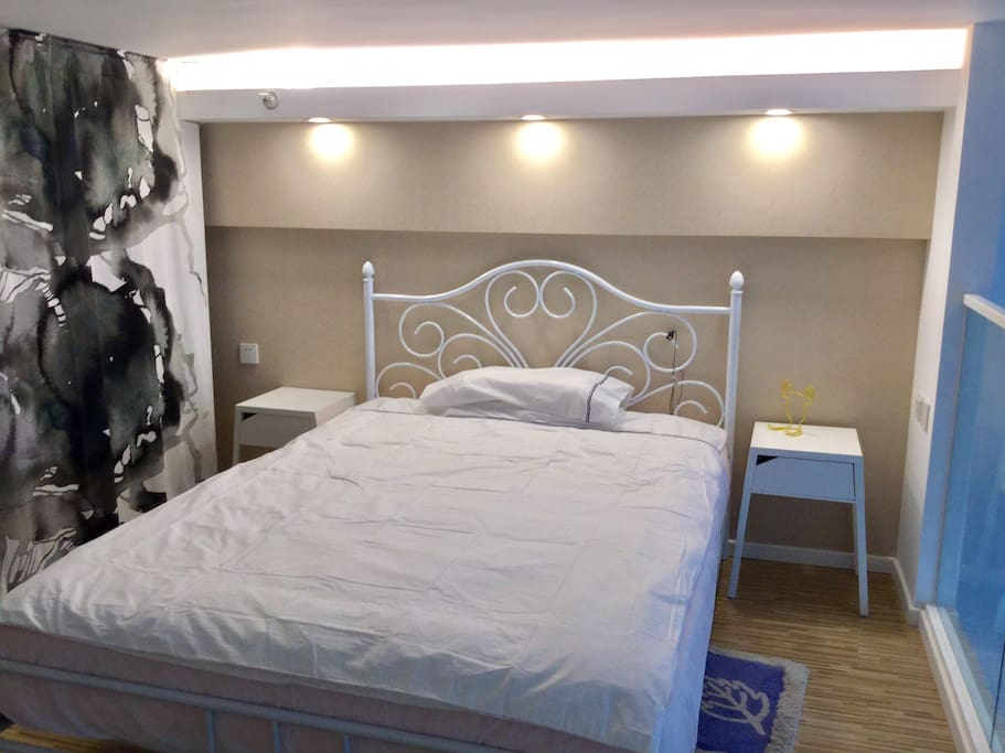 主卧的床及开放式衣柜(帘后)