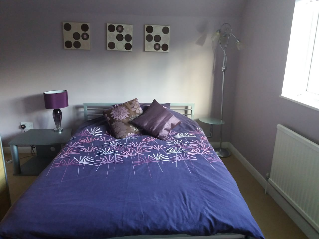 Large bright room.  Double bed with large window.  Bedside table and side lights.
