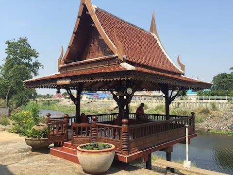 Traditionelles thailändisches Haus in Flussnähe