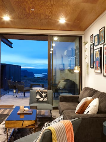 Living room, with floor to ceiling sliding doors and private patio showcasing views of Columbia river.
