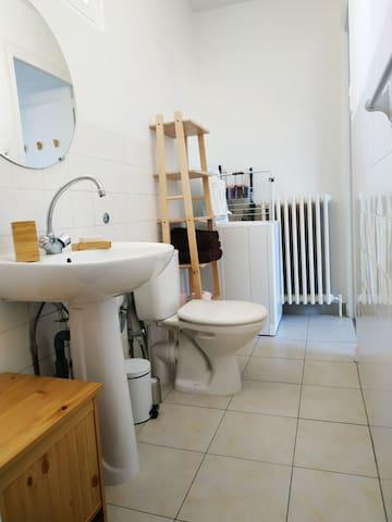 Salle de bains équipée d'un lave linge et étendoir, serviettes fournies