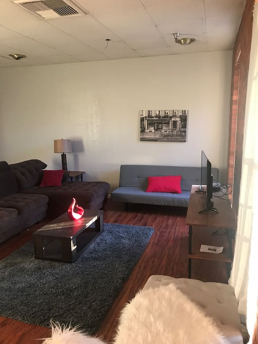 Living room area with futon that opens up into another bed..