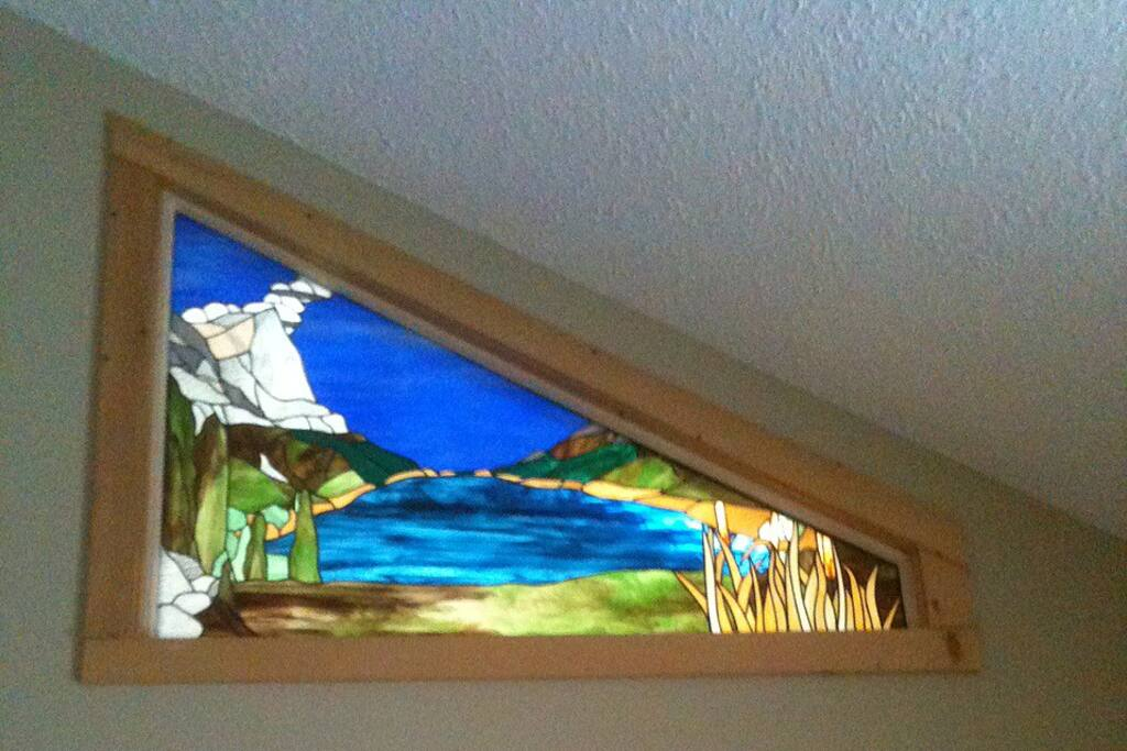 Stained glass window in Master bedroom lit from behind by a sky light